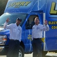 2 Lowry employees waving in front of truck