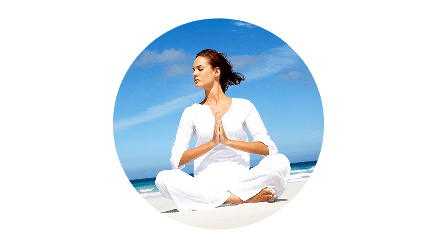 Woman wearing white meditating on the beach