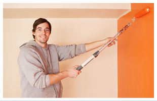 Man painting the wall with orange color