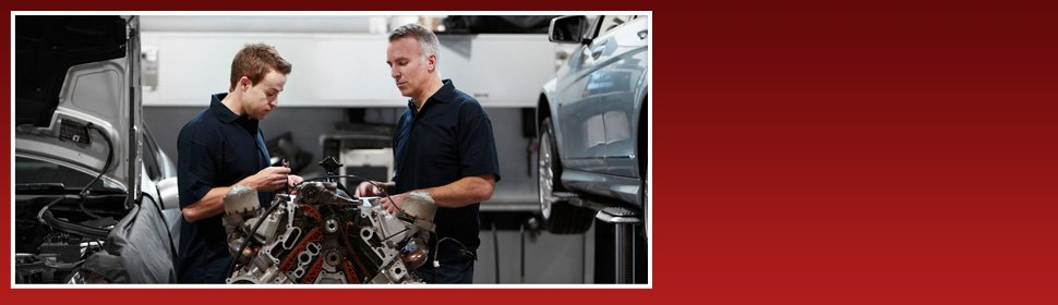 Two mechanics checking a car engine