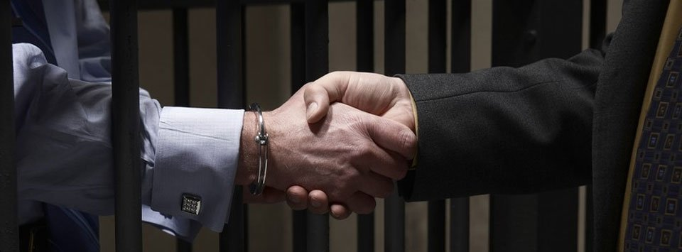 Man in the jail and lawyer shaking hands