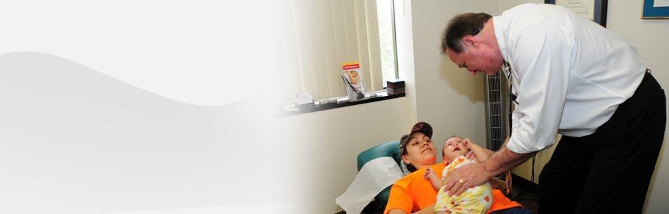 Chiropractor checking baby