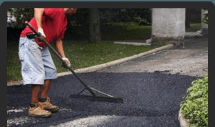 man raking asphalt