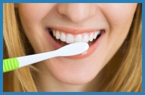 Woman smiling with toothbrush near her teeth