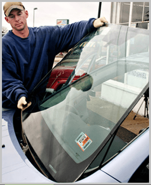 A mechanic installing a windshield