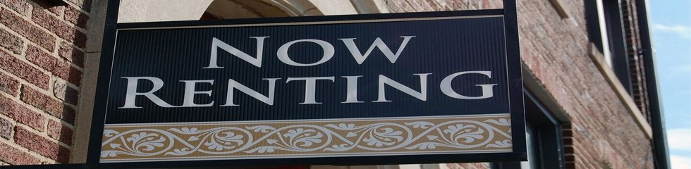 now renting sign on brick building