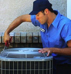A man repairing an air conditioning unit