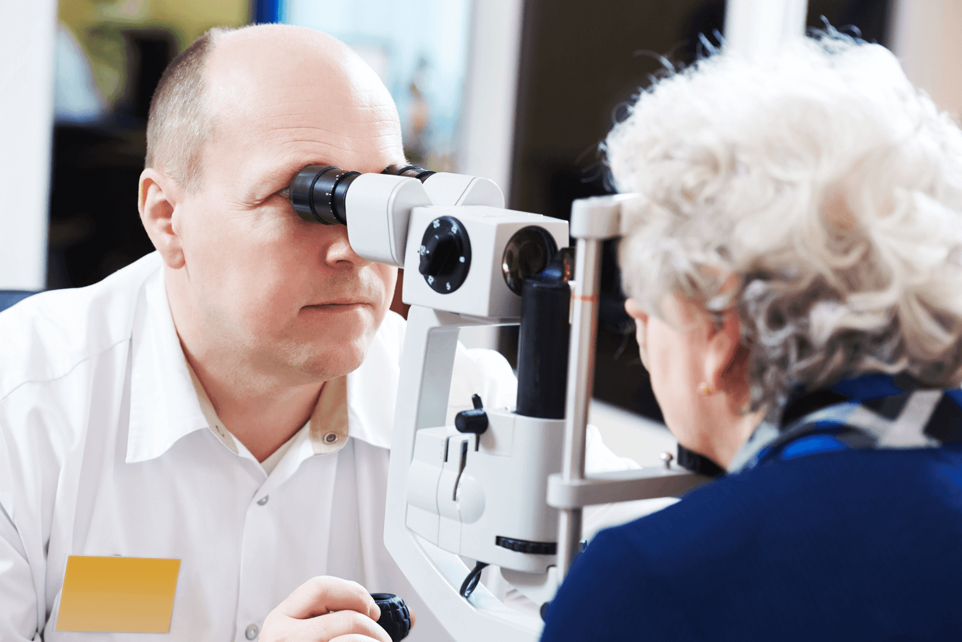 older woman getting an eye exam from doctor