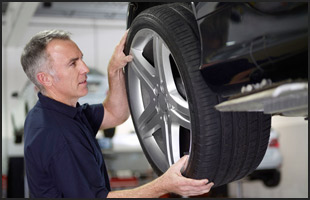 Man replacing a tire of an auto