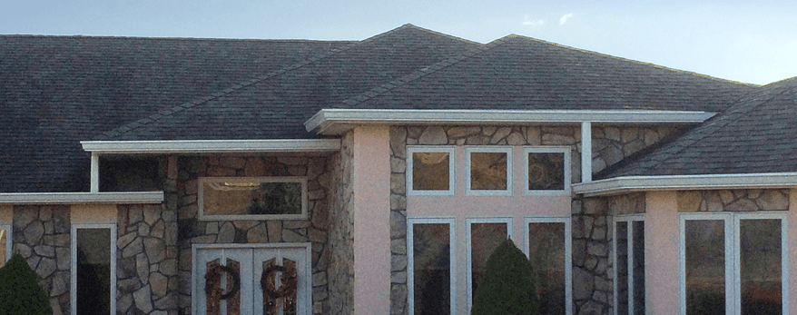 Pink and stone house with dark roof and white gutters