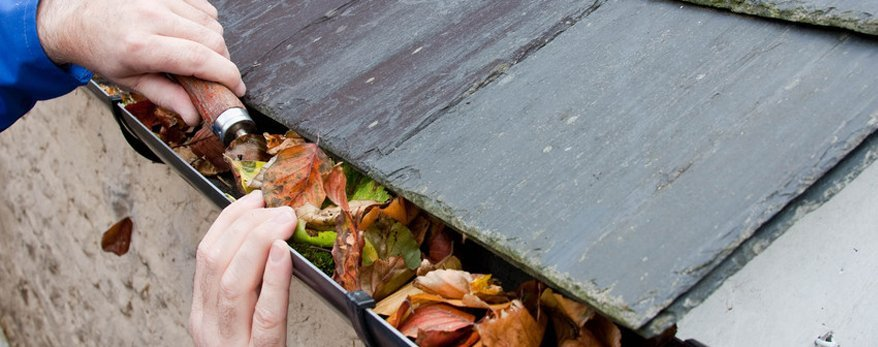 Man cleaning gutters filled with leaves