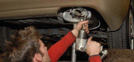 A man repairing a car's muffler