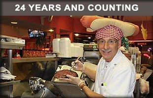 Man preparing pastrami sandwiches