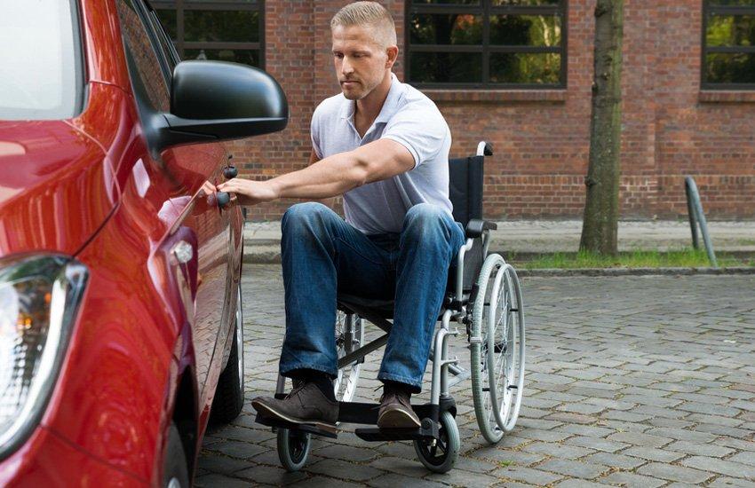 Man in wheelchair opening car door