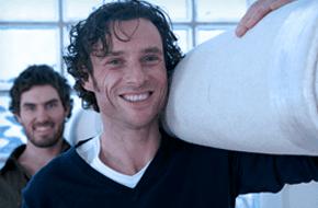 Two men carrying a big carpet
