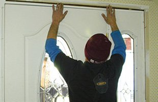 Man installing new white door