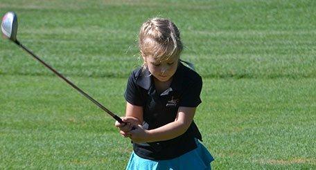 Young girl golfing
