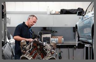 Technician testing car engine