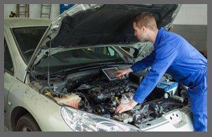 Technician testing car transmission