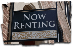 For Rent sign with scroll on brick building