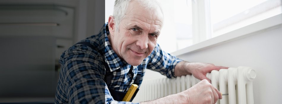 An electrician smiling while holding the heater