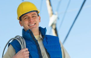 Electrician smiling while holding a bundle of wires
