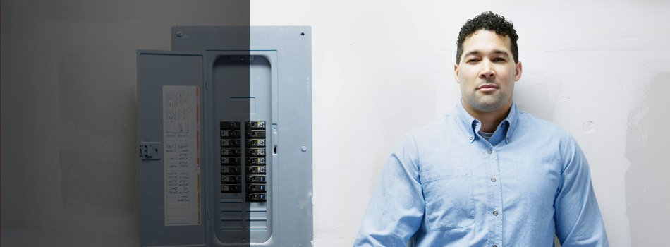 An electrician standing behind the fuse box