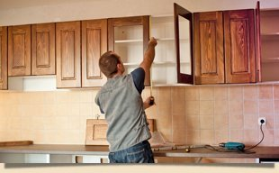 Guy Installing The Wooden Cabinets
