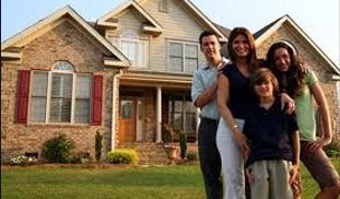 Happy family standingin front of their new remodeled house