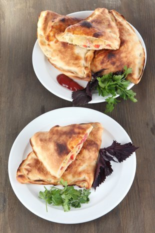 Different types of Calzones on a wooden table