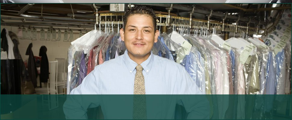 Man with dry cleaned clothes on the background