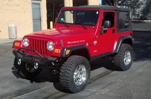 A clean red jeep with cover