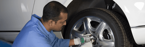 Man Installing A New Tire For A Auto
