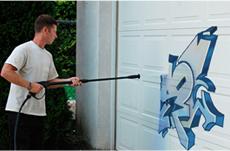 Man pressure washing the wall