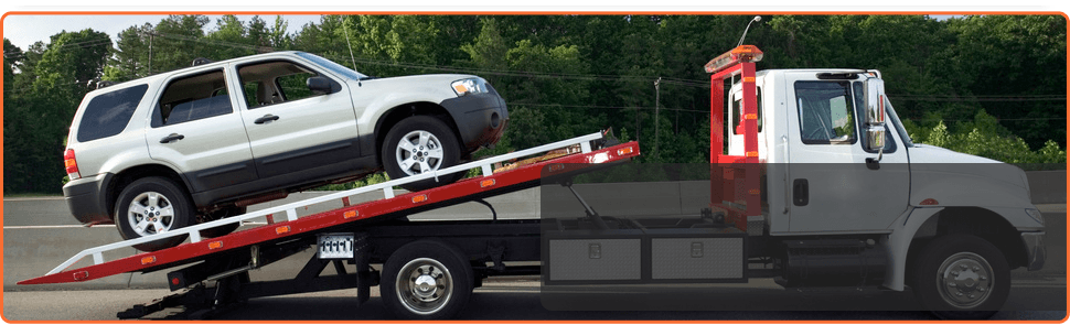 A tow truck is towing a SUV