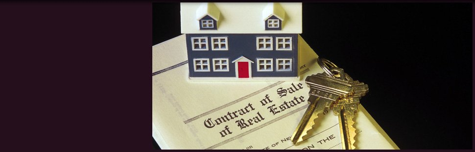A real estate contract of sale with a key on the top of it