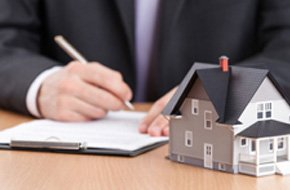 A landlord signs contract behind home architectural model