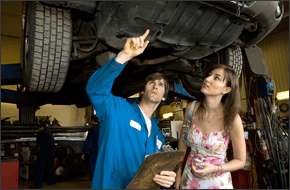 Auto mechanic checking car with his client