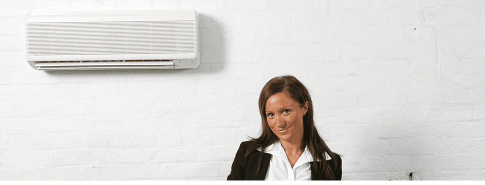 Happy lady at office & AC unit on the wall