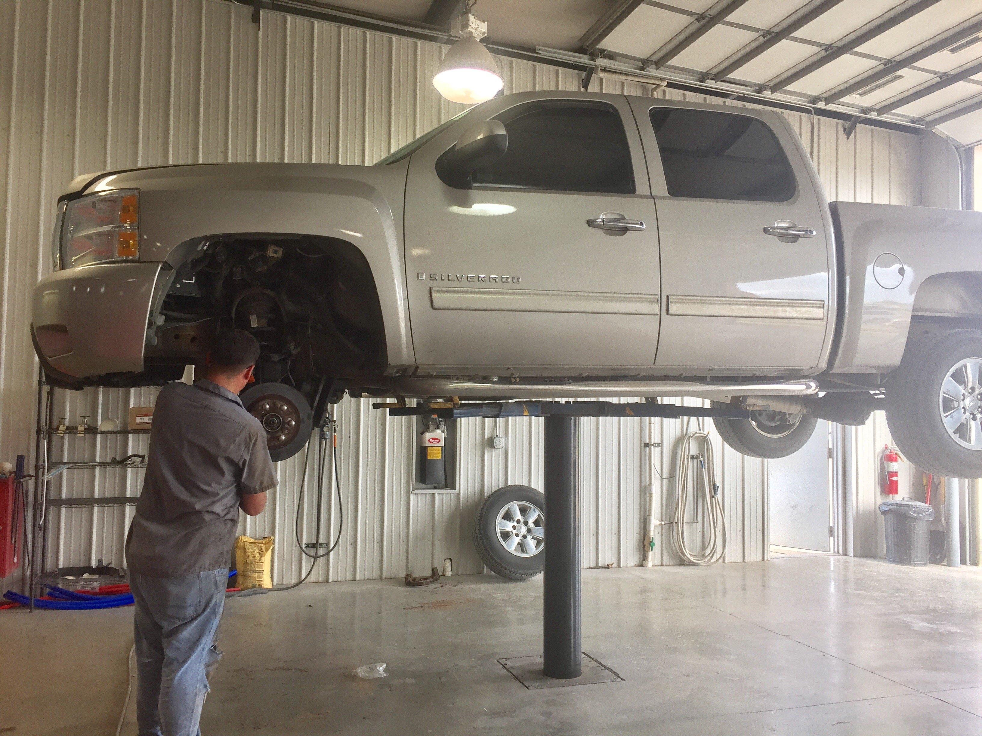 inside repair bay, grayish passenger truck on lift without tires, mechanic working on wheel