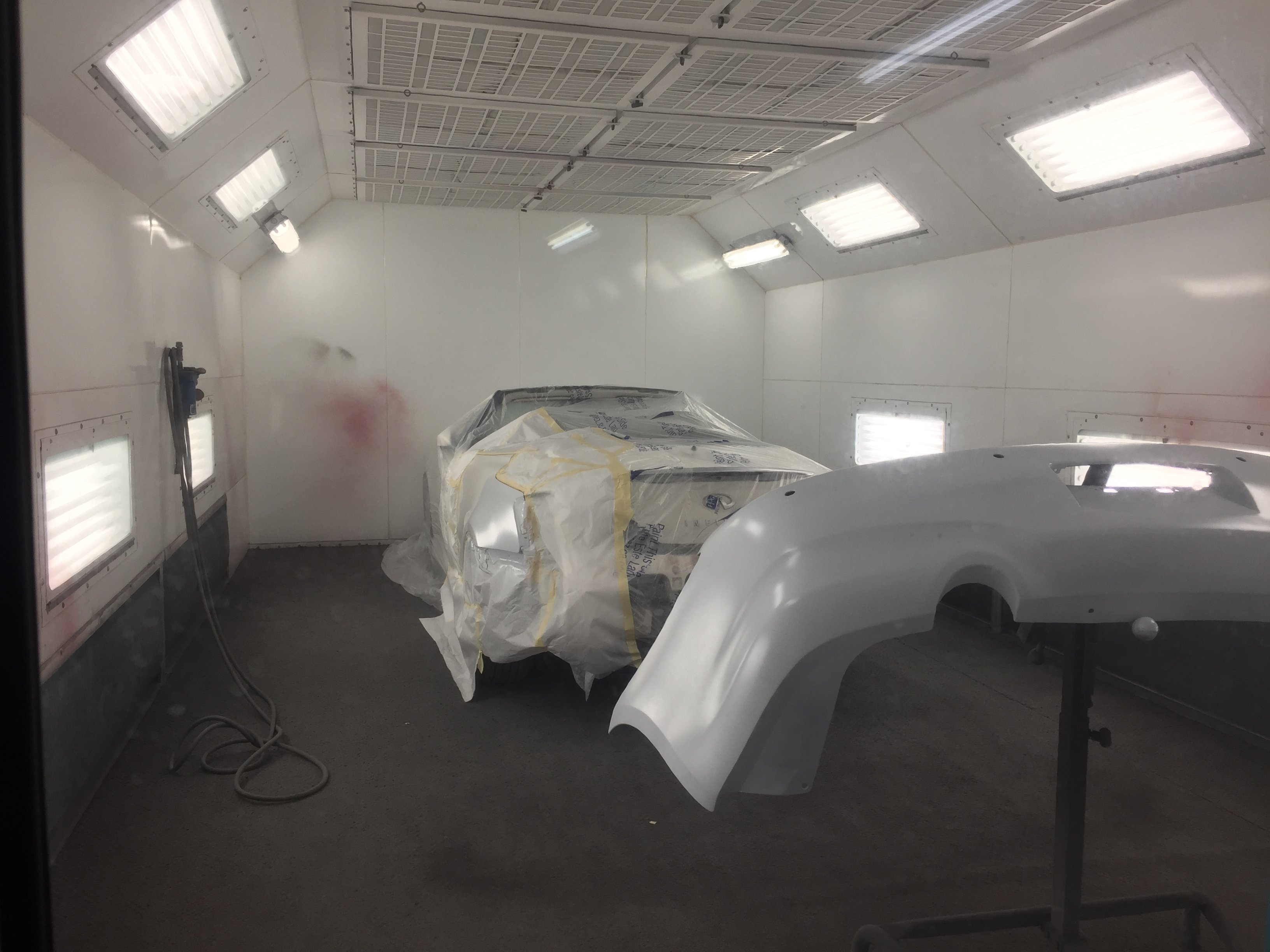 inside of painting bay, bumper with primer, rest of car taped and sheeted in background