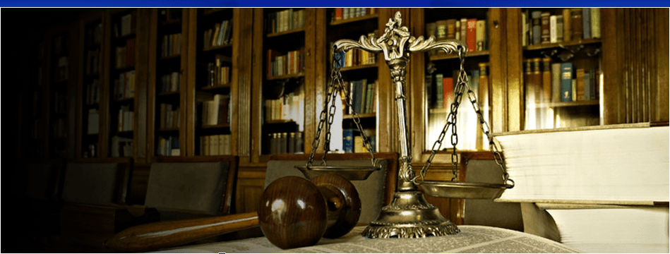 A scale and gavel on a table full of books