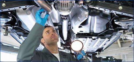 Auto technician checking transmission