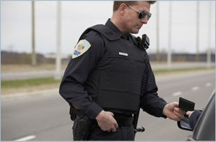 Police officer giving a ticket to a driver on a highway