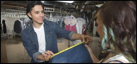 Tailor showing jeans measurement to female client in laundry