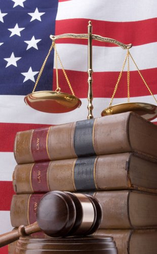The American flag with gavel, legal books and the gold justice scales