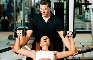 Woman being supported by gym assistant