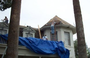 Roofing contractors standing top of the house