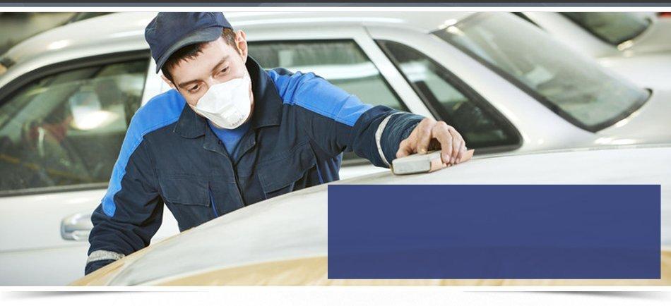 professional repairman worker in automotive industry sanding metal caer roof before painting at bodywork