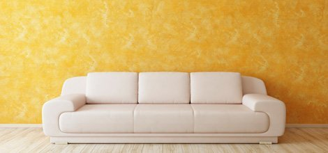 A wall with yellow paint design and a couch